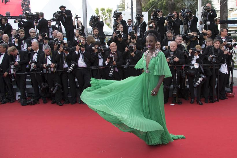 """[12:50] Actress Lupita Nyong'o poses on the red carpet as she arrives for the opening ceremony and the screening of the film """"La tete haute"""" out of competition during the 68th Cannes Film Festival"""