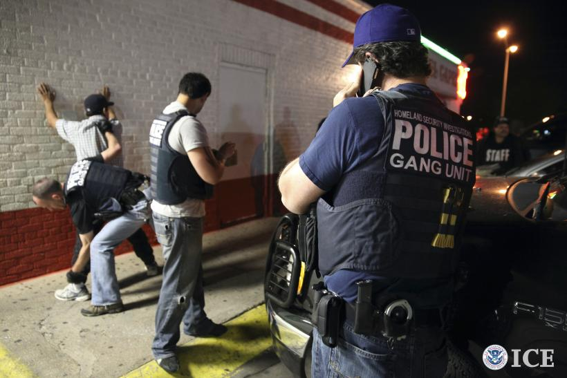 Immigration officials detain a suspect during a raid