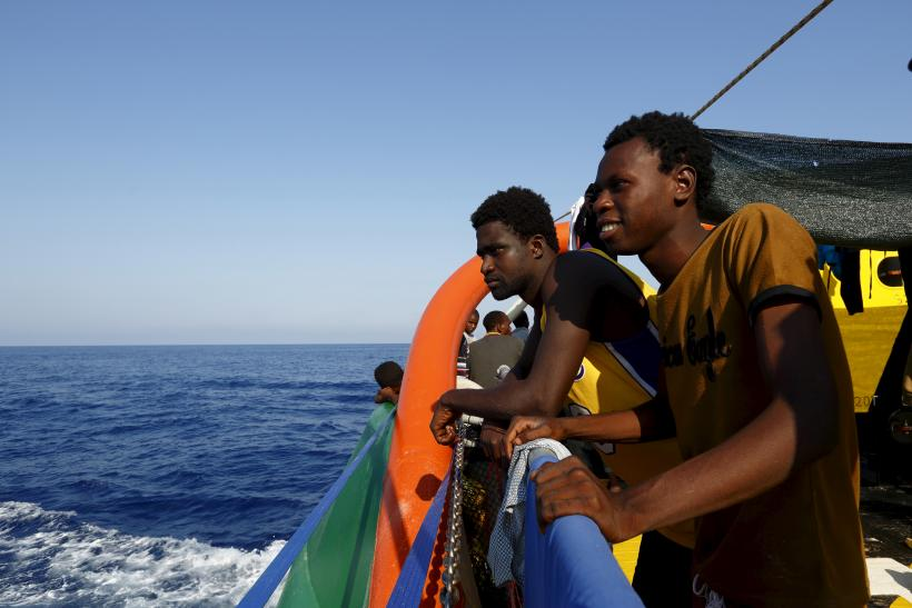 Migrants look out across the Mediterranean after being rescued by a European ship