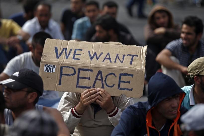 A Syrian man holds a banner asking for peace.