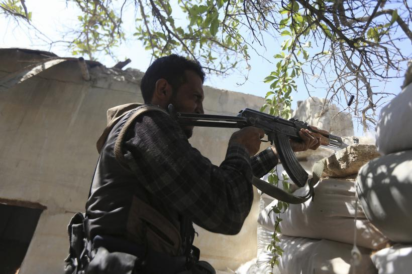 A Free Syrian Army fighter fires a rifle
