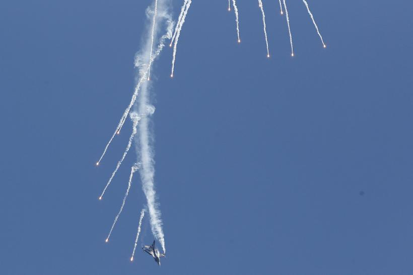 A Turkish F-16 fires maneuvers during an airshow