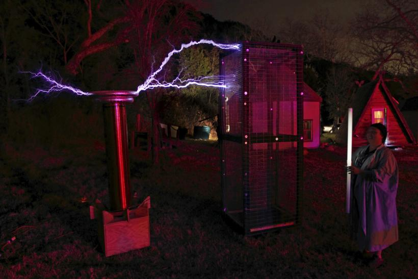 A person demonstrates the power of the Faraday cage