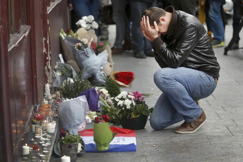 A man weeps as he pays his respects outside a restaurant in central Paris