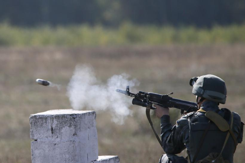 A Ukrainian soldier fires a weapon during a drill