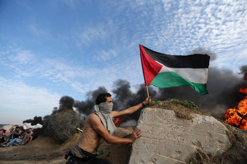 A protester plants a flag during clashes with Israel