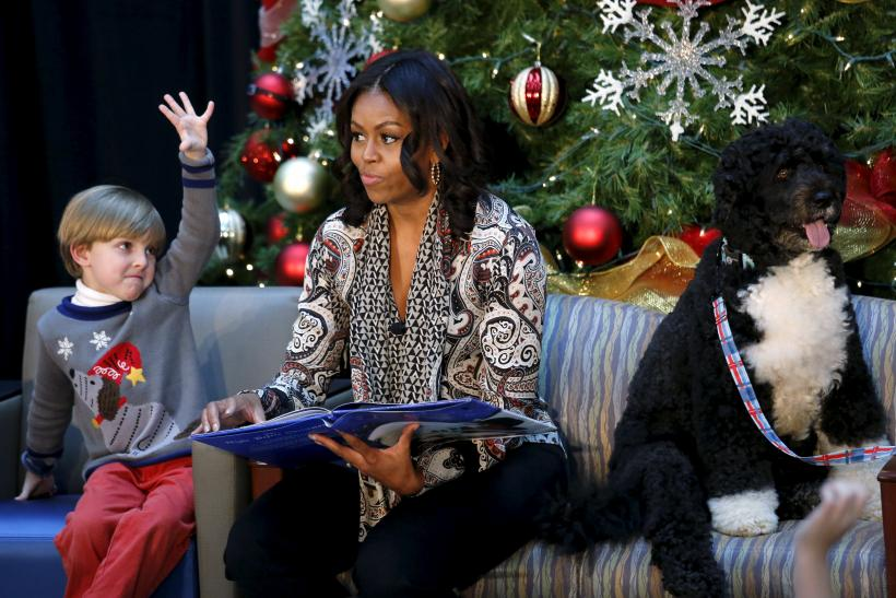 """Patient Stephen Orzechowski, 6, raises his hand as First Lady Michelle Obama reads """"T'was the Night Before Christmas"""" to children during her visit to Children's National Health System"""