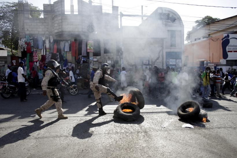 Police officers kick tires during clashes with civilians in Haiti.