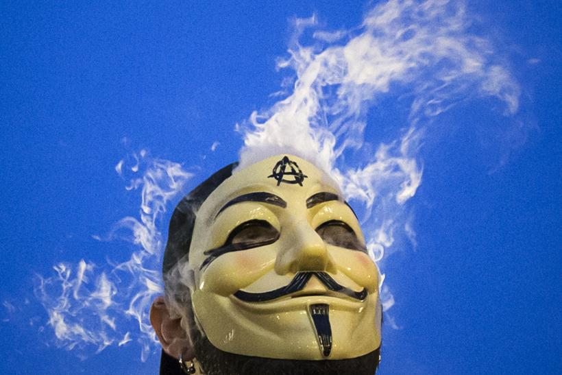 A man smokes behind a Guy Fawkes mask at a protest.