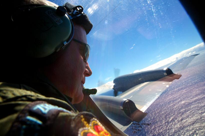 An airmen looks out at the ocean in the search for MH370.