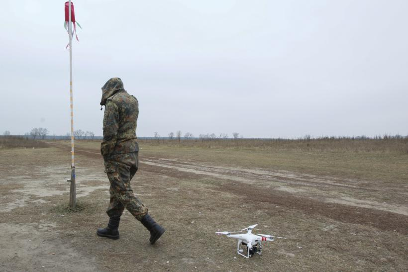 A drone rests as a Ukrainian soldier walks by.