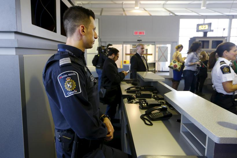 A Canadian border official watches over a terminal in Toronto.