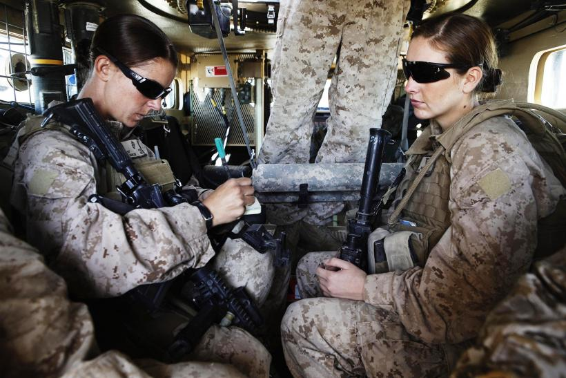 Two female US marines travel inside an armored vehicle in Afghanistan.