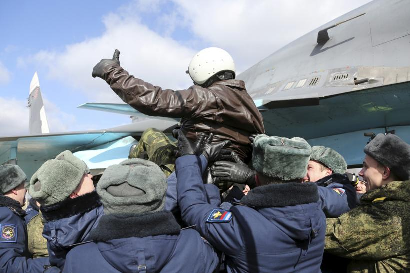 A Russian pilot is lofted in the air after returning from the Syrian war.
