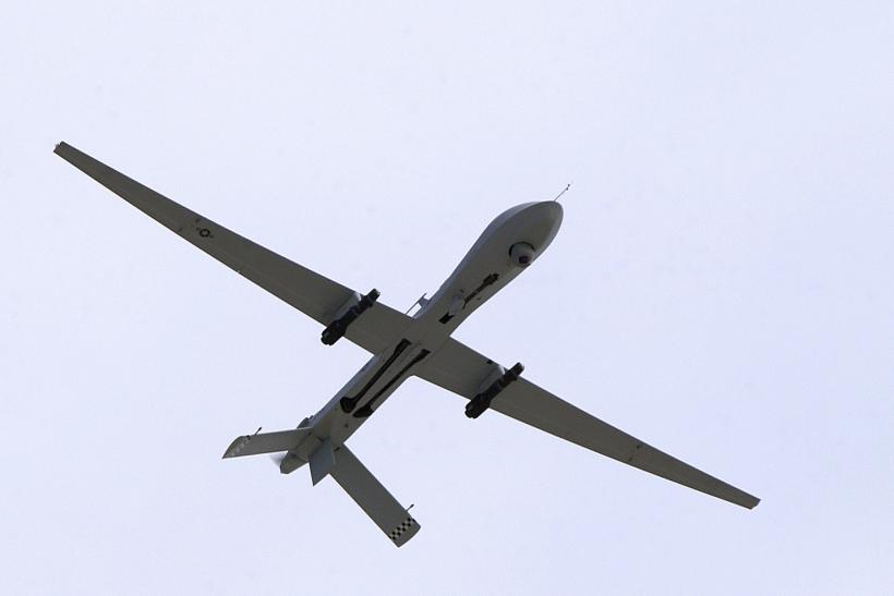 A predator drone armed with hellfire missiles flies over a military base in Nevada.