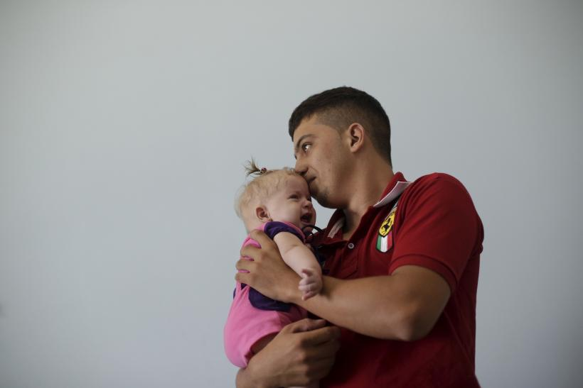A single father holds his four-month old daughter in Brazil.