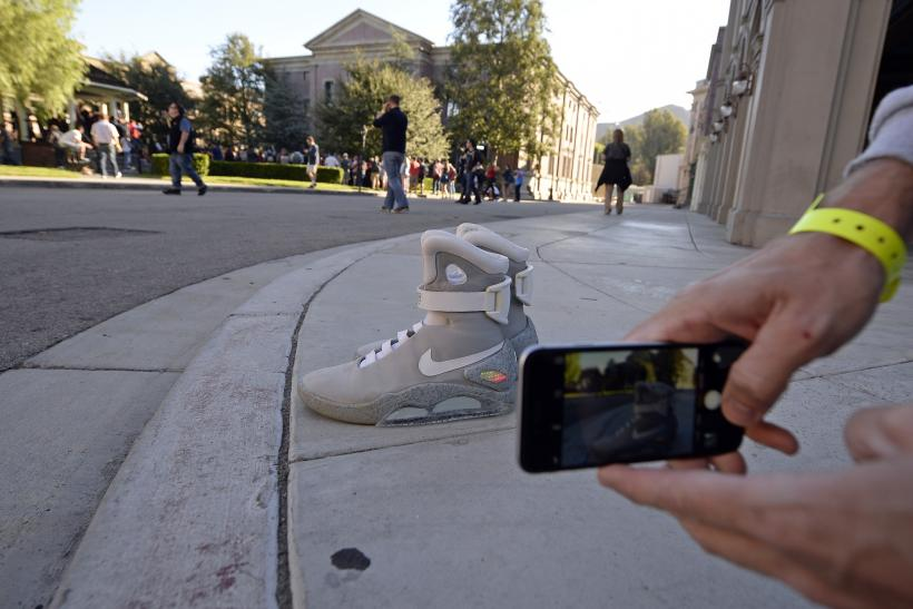 6e847a0ec0ade A fans takes a photograph of Nike 'Back to the Future' Air Mag sneakers in  the Hill Valley Courthouse square in the back lot of Universal Studios  during ' ...