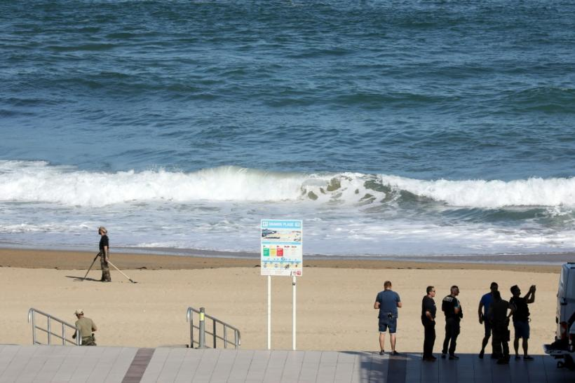 French bomb squad officials sweep an area of beach in Biarritz