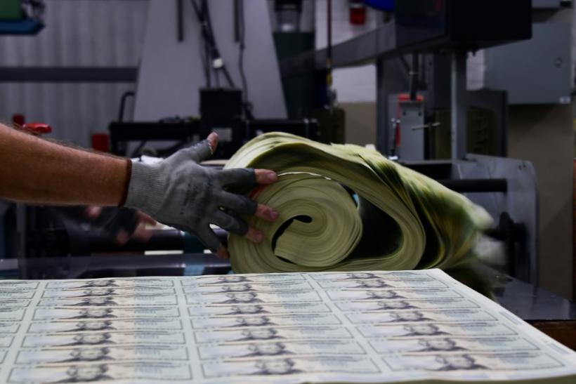 A US Treasury Bureau of Engraving and Printing employee in Washington DC weighs a pack of freshly printed sheets of $20 notes valued at $200,000