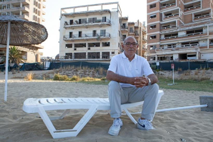 Pavlos Iacovou sits near the ghost town of Varosha, fenced off by occupying Turkish soldiers in 1974