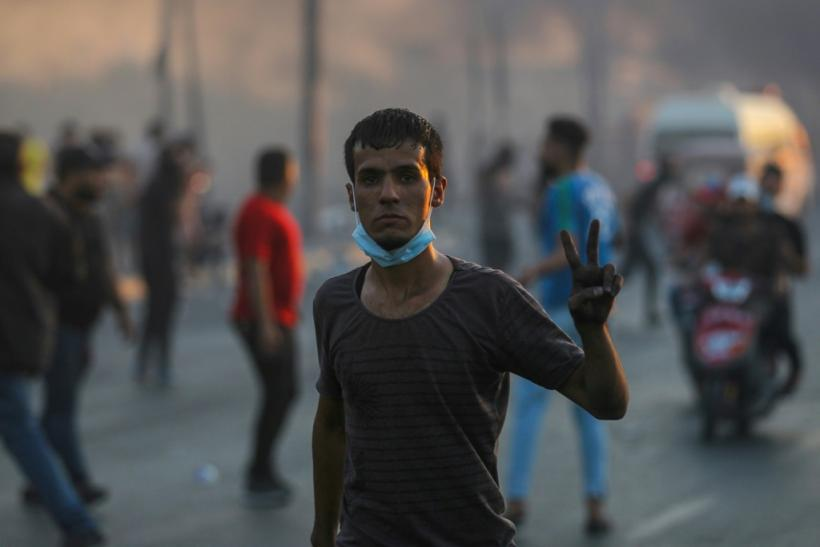An Iraqi demonstrator flashes the victory sign during a demonstration in Baghdad Saturday