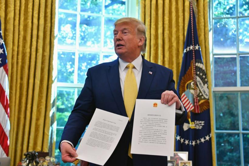 US President Donald Trump shows a letter from Chinese President Xi Jinping as he announces and initial deal with China while meeting the special Envoy and Vice Premier of the People's Republic of China Liu He Special Envoy and Vice Premier of the People's
