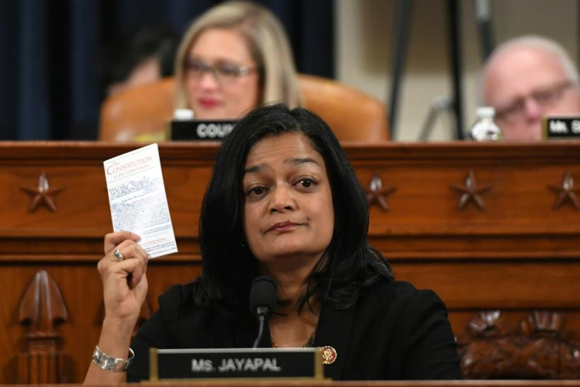 Democratic lawmaker Pramila Jayapal holds up a copy of the Constitution as she votes to impeach President Donald Trump