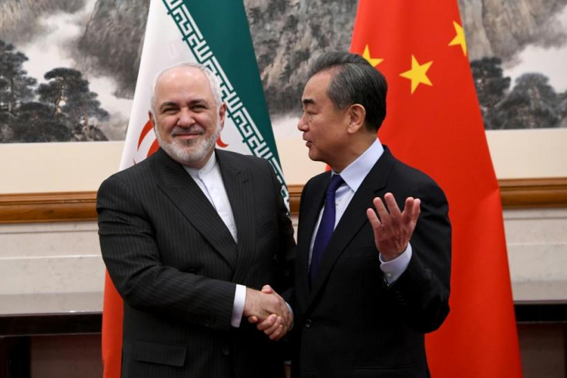 China's Foreign Minister Wang Yi shakes hands with his Iranian counterpart Mohammad Javad Zarif during their meeting in Beijing in December 2019