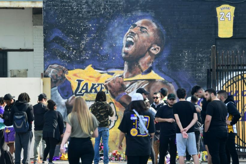 Fans gather to mourn the death of NBA legend Kobe Bryant at a mural near Staples Center