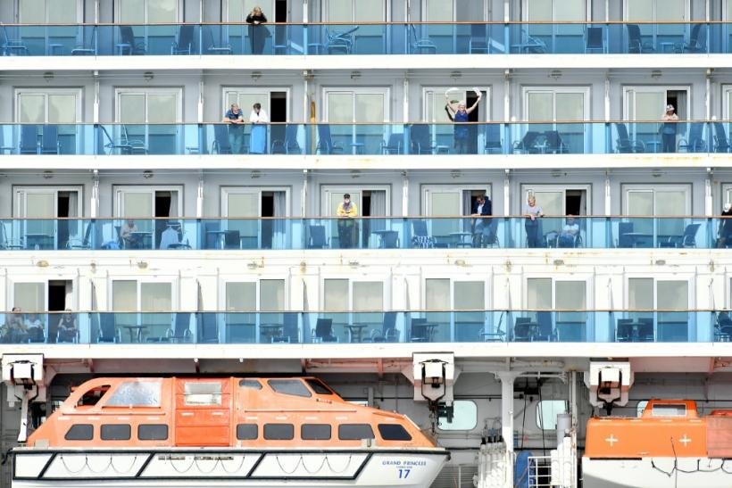 A woman waves as others look out from aboard the Grand Princess cruise ship, operated by Princess Cruises, as it maintains a holding pattern about 25 miles off the coast of San Francisco, California