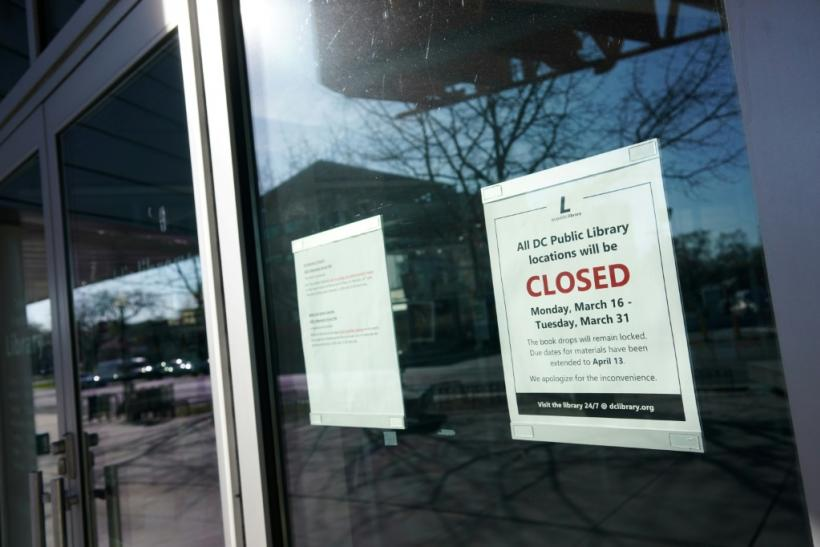 """A """"closed"""" sign is viewed on the door of the Tenley/Friendship DC Public Library on March 16, 2020, in Washington, DC"""