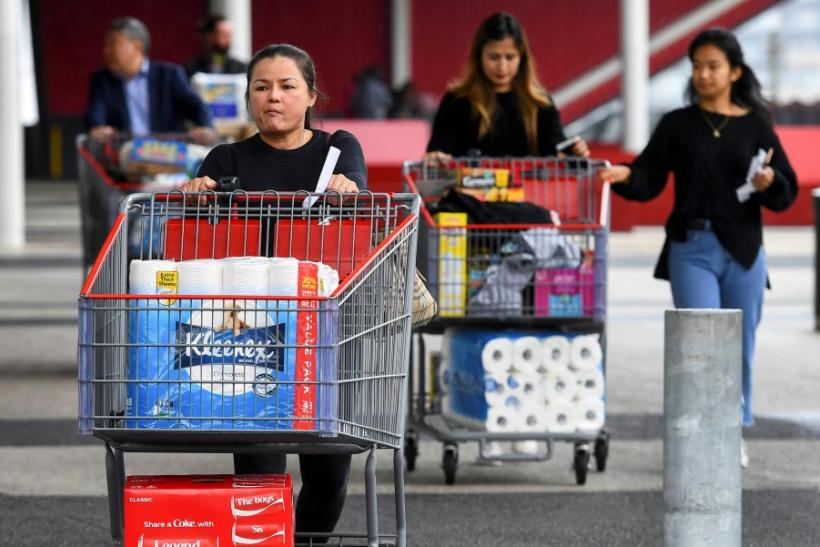 People leave a Costco warehouse with rolls of toilet paper amongst their groceries in Melbourne on March 5, 2020