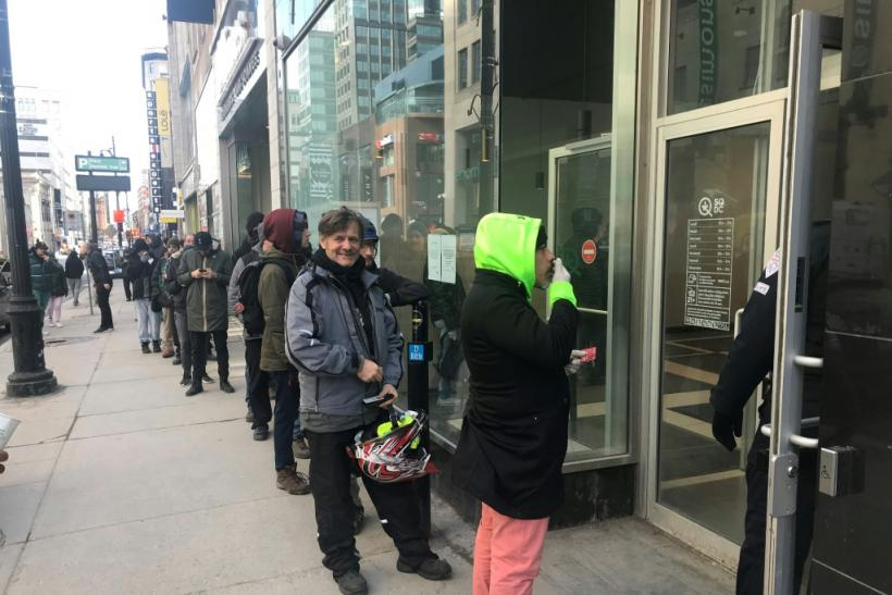 Cannabis consumers line up outside a Montreal sales point for the mood-altering drug March 18, 2020