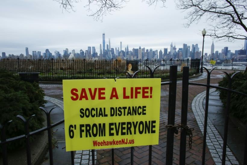 A sign encouraging social distancing to stop the spread of coronavirus is displayed in a park in New Jersey, with the New York city skyline in the background