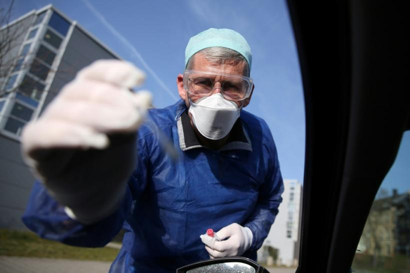 German doctor Michael Grosse takes a sample from a car driver at a drive-through testing point for the coronavirus in Halle, eastern Germany