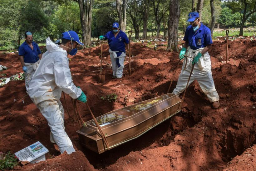 Four coffins are lowered into a single grave: one confirmed coronavirus death, and three suspected