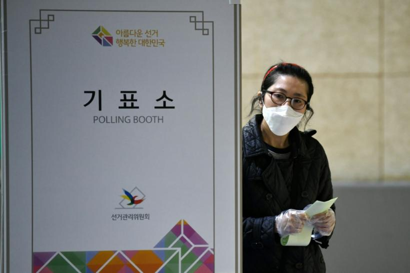 A South Korean woman casts her ballot for the parliamentary elections at a polling station in Seoul on April 15