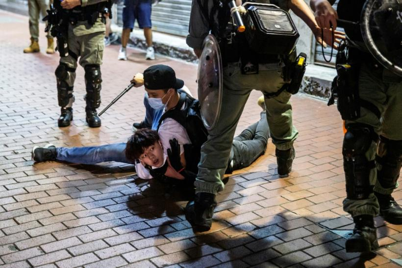 A Hong Kong pro-democracy demonstrator is held on the ground before getting arrested by police during a protest