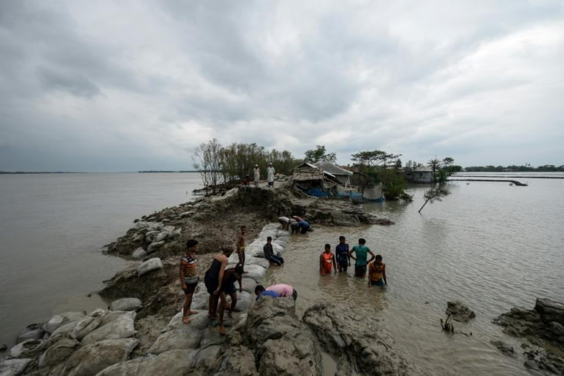 Volunteers and residents work to repair a damaged dam following the landfall of Cyclone Amphan in Burigoalini, Bangladesh, on May 21, 2020