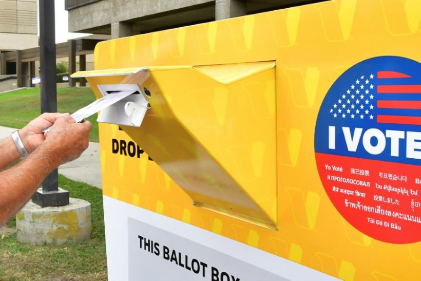 A voter drops a ballot for the 2020 US elections into an official drop box in Norwalk, California
