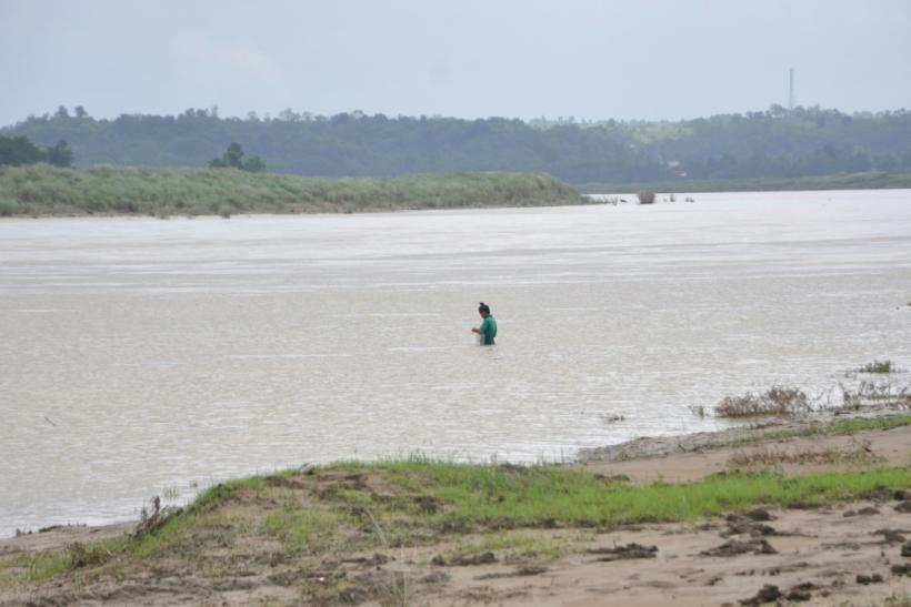 A man fishes in a swollen river caused by heavy rains north of Manila, ahead of Typhoon Goni's landfall in the Philippines