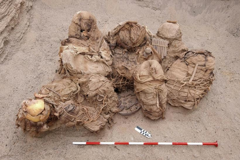 A handout picture released by Peruvian gas company Calidda, shows objects, food, artifacts and ancient funeral bundles containing the remains of eight people unearthed by workers