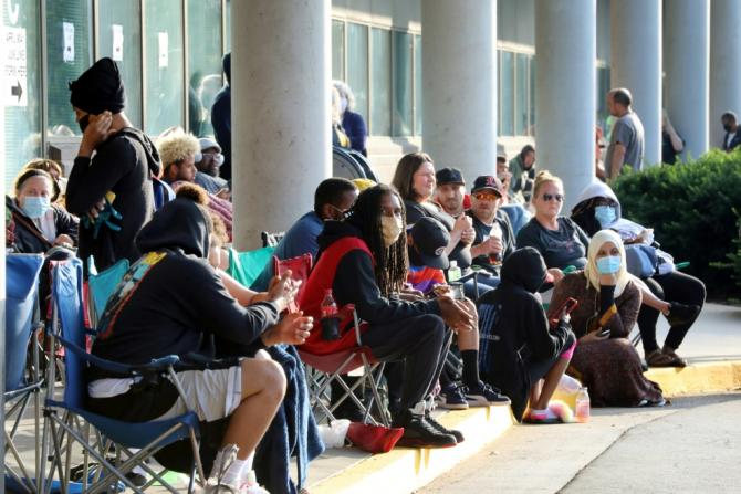 Hundreds of unemployed people wait outside the Kentucky Career Center in Frankfort, Kentucky for help with their unemployment claims