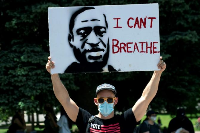 A demonstrator holds up a poster with a rendition of George Floyd on May 30 in Denver
