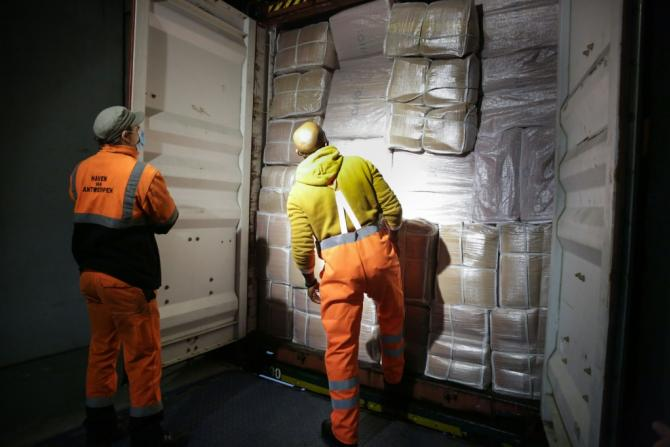 Dock workers open the back of a lorry at the customs to verify its load, at the port of Antwerp. Grenade explosions, shootings and even kidnapping of children: drug trafficking is generating a violent crime wave