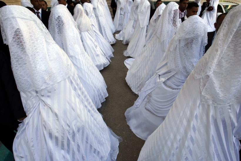 Brides and grooms pose during a mass wedding ceremony in Amman July 15, 2011. A Jordanian Islamic charity organized a mass wedding for 72 couples unable to afford expensive ceremonies
