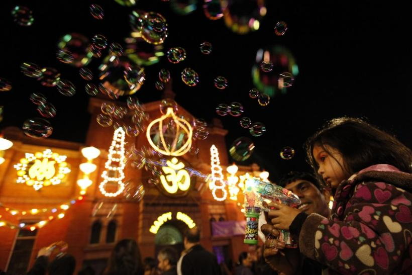 A girls shoots bubbles from a gun during the start of Diwali celebrations in Leicester