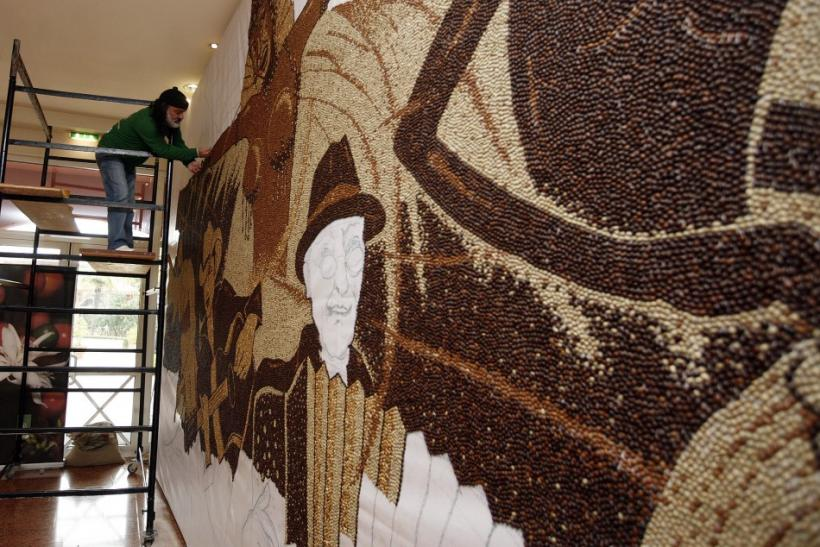 Artist Strati working on his coffee bean mosaic in November. Reuters