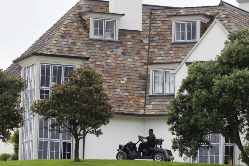 A security guard patrols the grounds after a police raid at Dotcom Mansion, home of accused Kim Dotcom, is seen in Coatesville