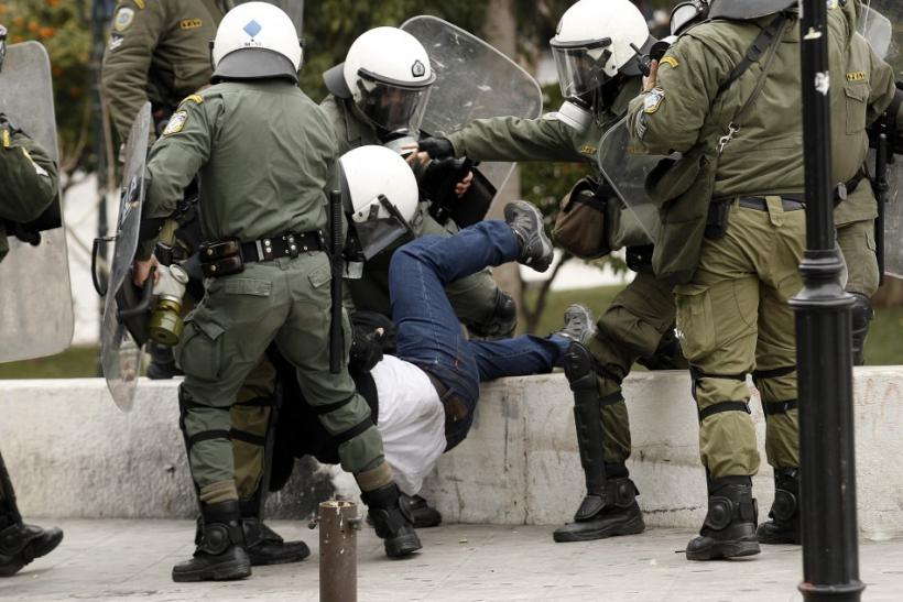 Police drag off a protester during demonstrations in Athens Friday